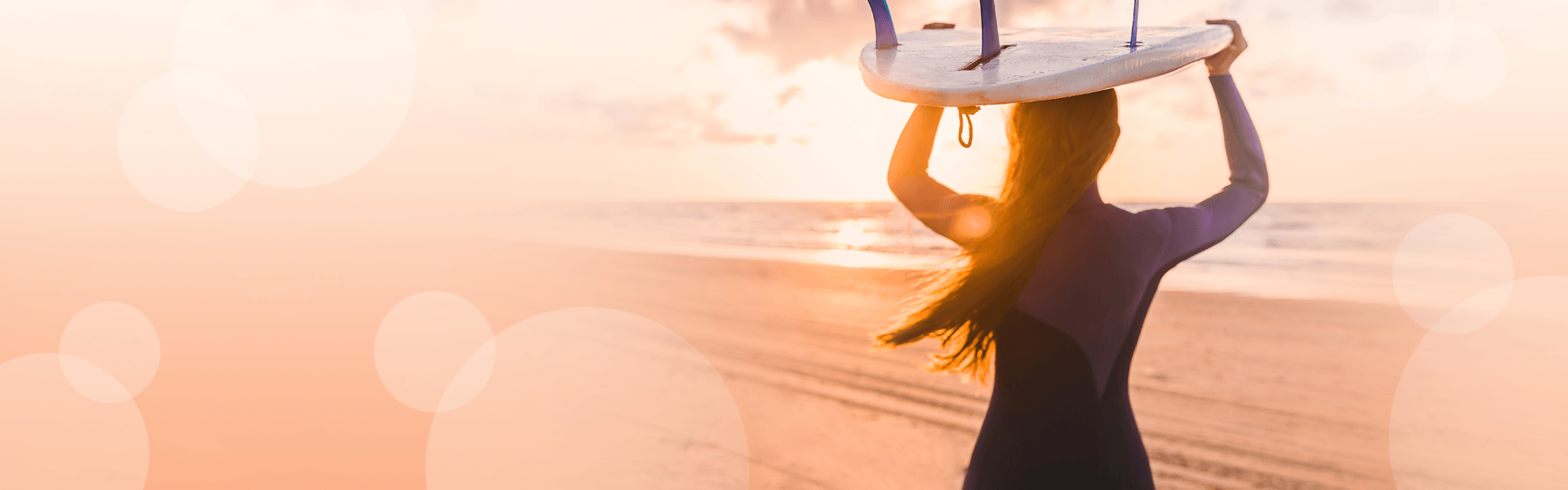 Woman on beach, with surfboard, looking out at sunset.